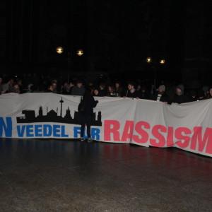 """Ein Transparent mit dem Schriftzug """"Kein Veedel für Rassismus"""" auf der Abschlusskundgebung der Gegendemo vor dem Kölner Dom."""