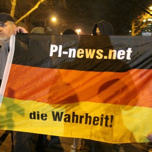 """Eine Deutschlandflagge mit der Adresse des rechten Blogs """"PI-News"""". Es zeigt, was für Leute bei Dugida waren. Aus der Mitte kamen sie jedenfalls nicht."""