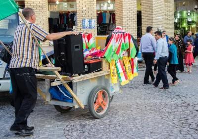 Ein fahrender Verkäufer mit Flaggen, Schals und weiterem Fanmaterial in den Farben Kurdistans und der Regierungspartei PDK
