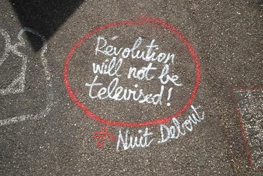 """Kreidekreis auf der Straße in dem steht: """"Die Revolution wird nicht im Fernsehen übertragen."""""""