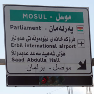 """The Battle of Mosul"". Foto:  Jeffrey Beall, licensed under CC BY 2.0, Mosul sign, via flickr.com"