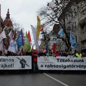 Proteste in Ungarn. Zwei Transparente an der Spitze der Demonstration samt Dutzenden Fahnen.